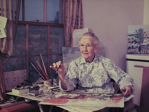Photograph of an old woman, Grandma Moses, at her painting table with a canvas and paint brushes on the table in front of her.