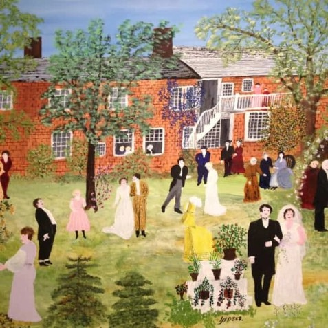 A painting of a wedding party where the bride and groom are standing together facing the viewer on the right side, the guests are in various groups around a yard in front of a big brick house. This painting is called Wedding by Grandma Moses.