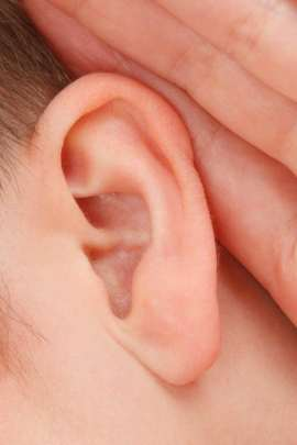 Image of an ear close up with fingers held behind the ear as if listening.