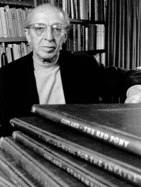 Black and white photo of older man who is mostly bald with a fringe of white hair wearing glasses and a suit jacket behind books of his musical works, Aaron Copland.