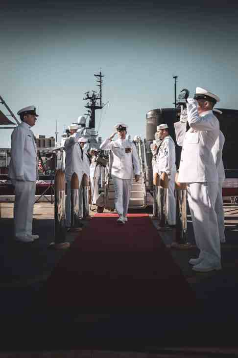 Image of Navy sailors standing in two rows facing each other and saluting while one walks through.