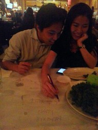 Sitting across dad and writing wishes upside down; Amaroni's Little Italy