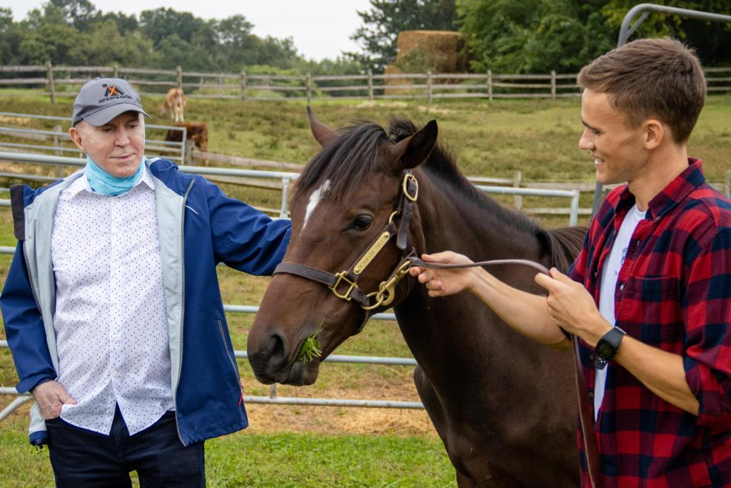 Two men enjoy the horse racing experience at the farm by interacting with their young horse.