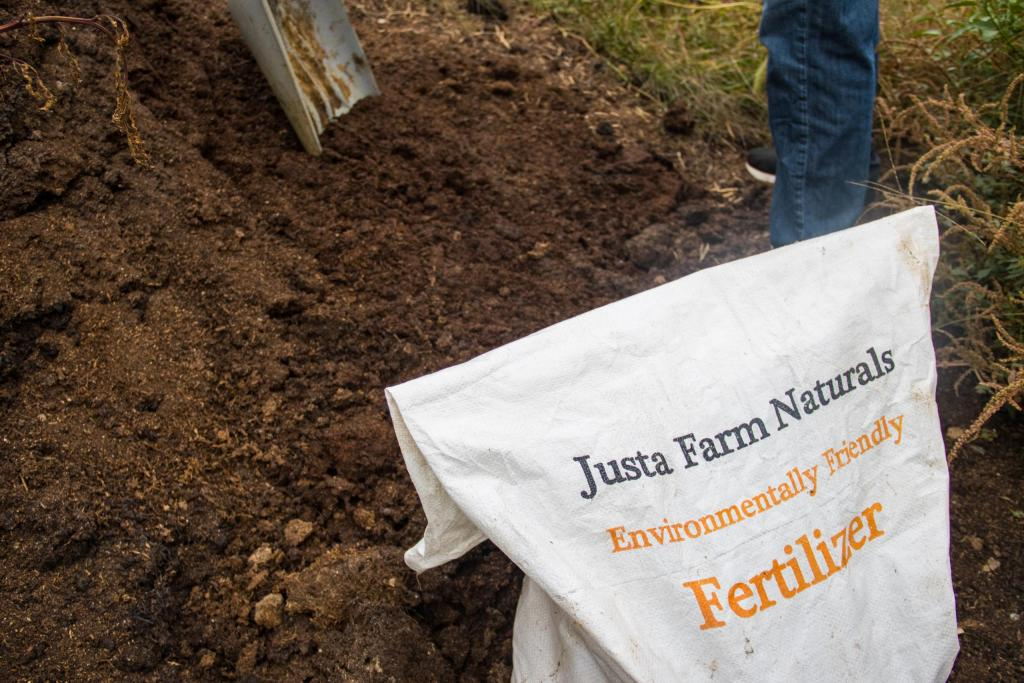 Justa Farm Naturals branded bag in front of a pile of organic natural fertilizer.