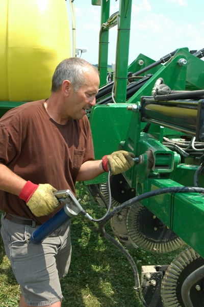 Rod greasing a Redball sidedress bar used in the Farm Journal Test Plots