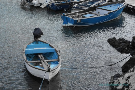 Blue boats anchored in the harbor's winter waters
