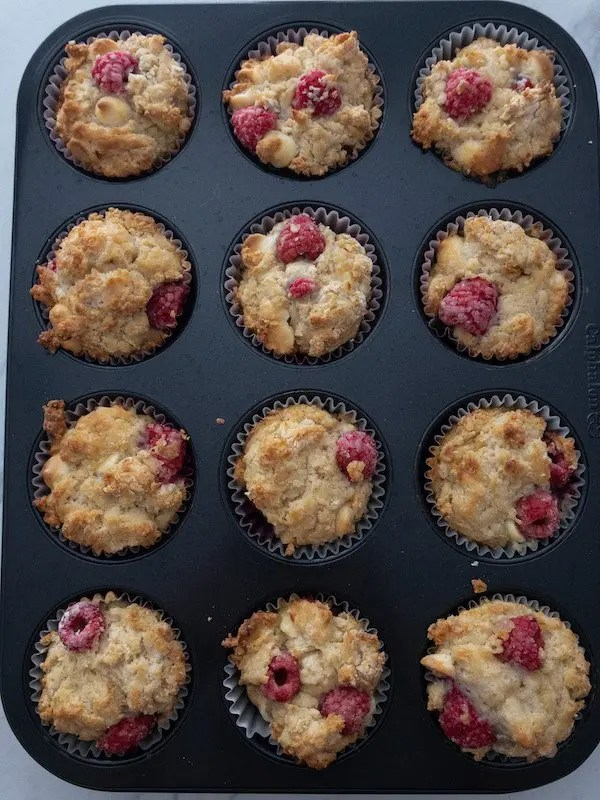 Raspberry muffins in a black muffin tin