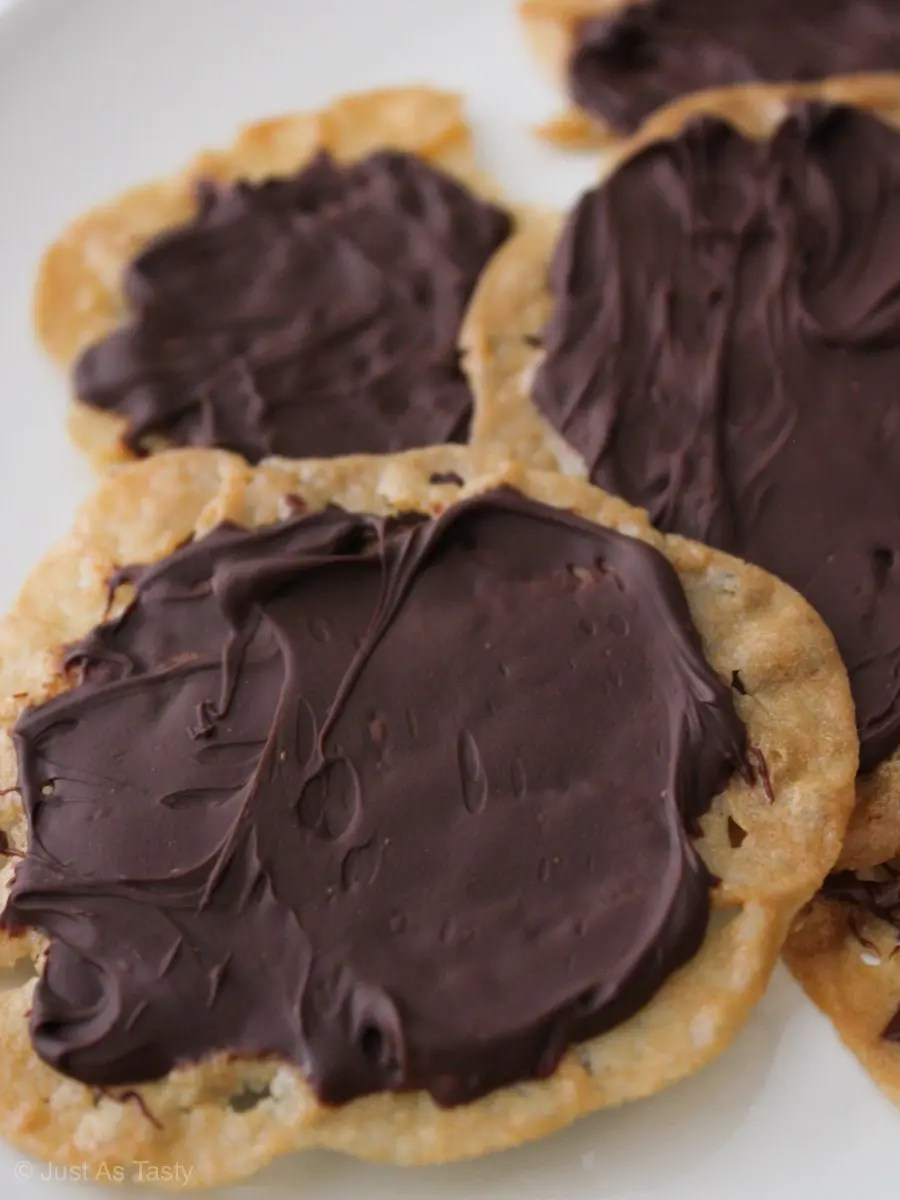Chocolate covered lace cookies on a white plate