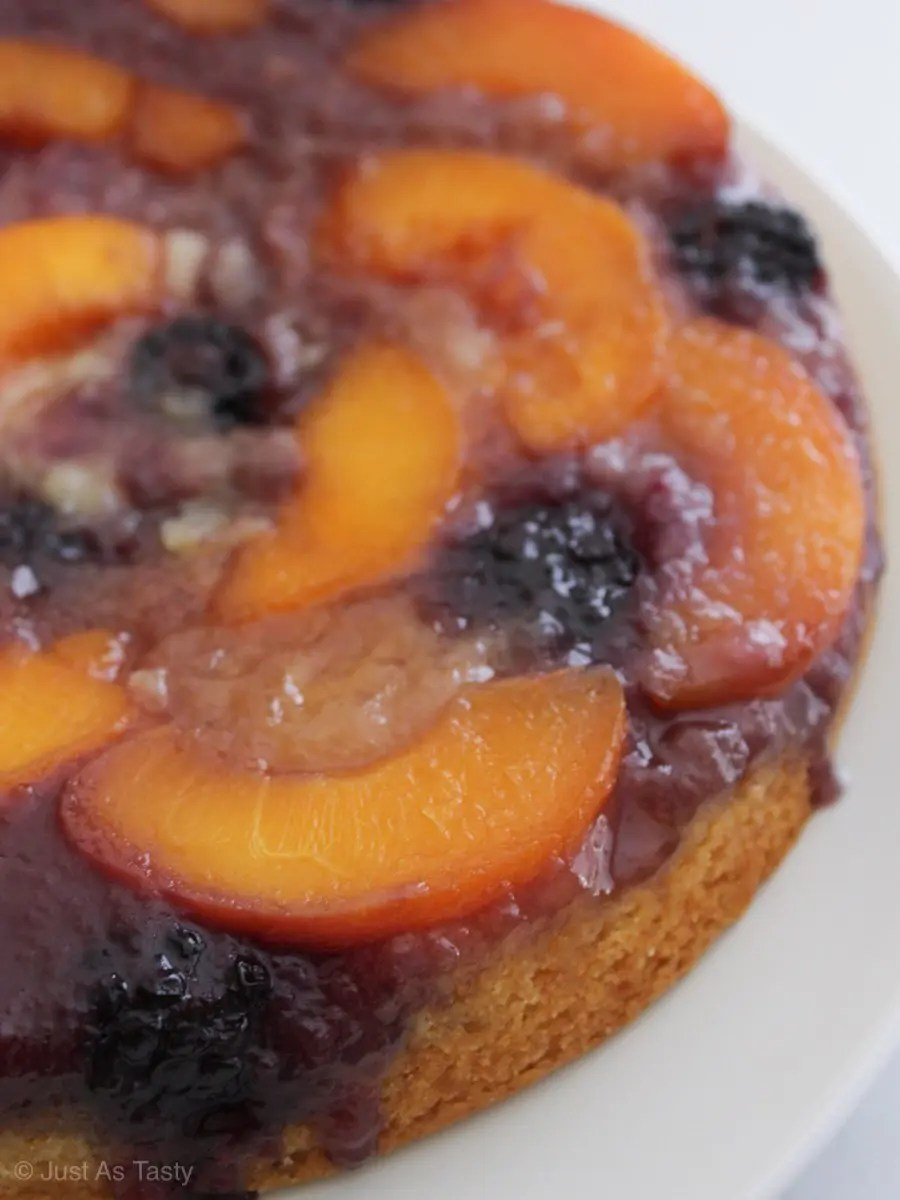 Peach upside down cake cake topped with peaches and blackberries.