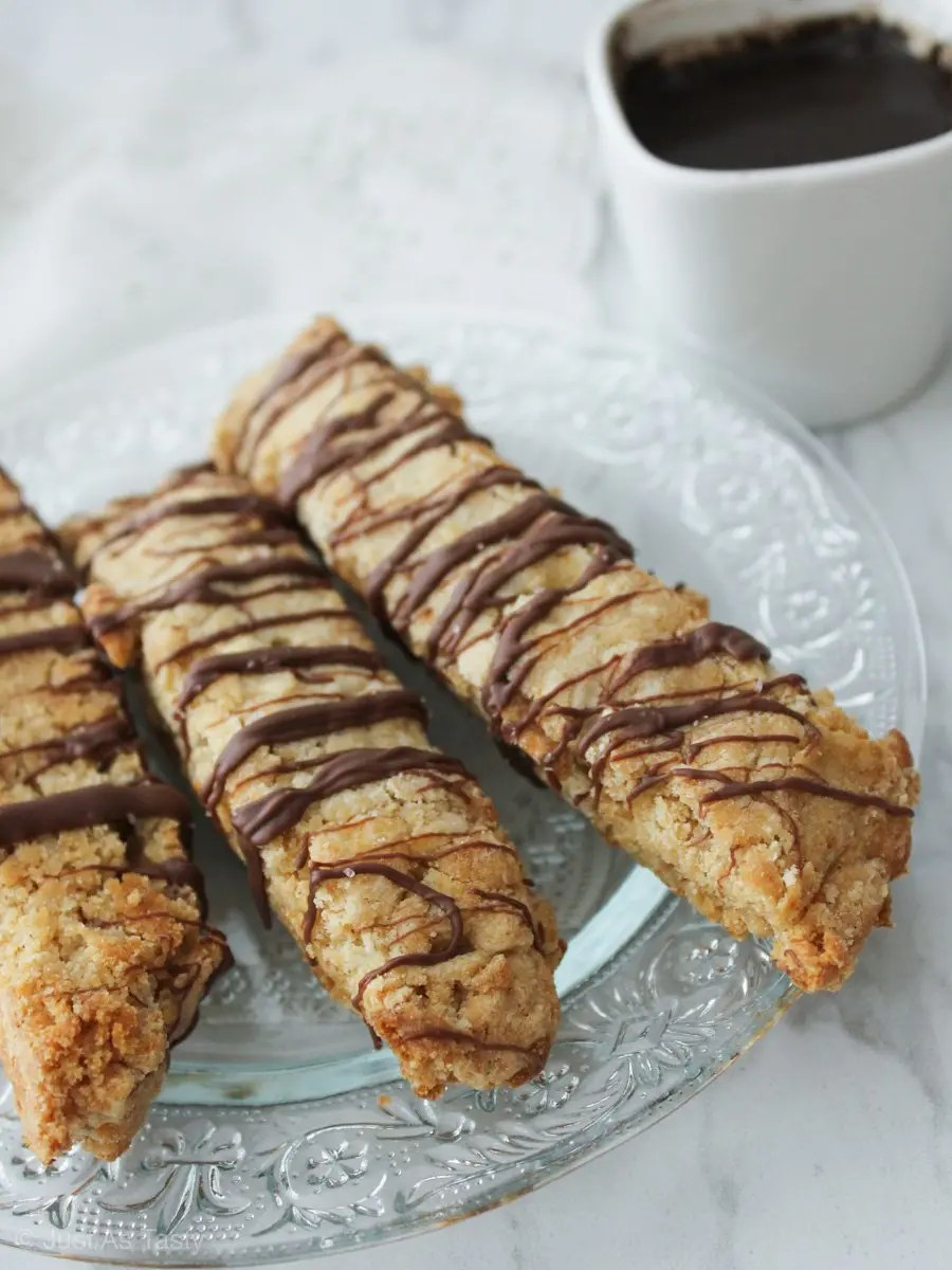 Chocolate drizzled biscotti on a glass plate.