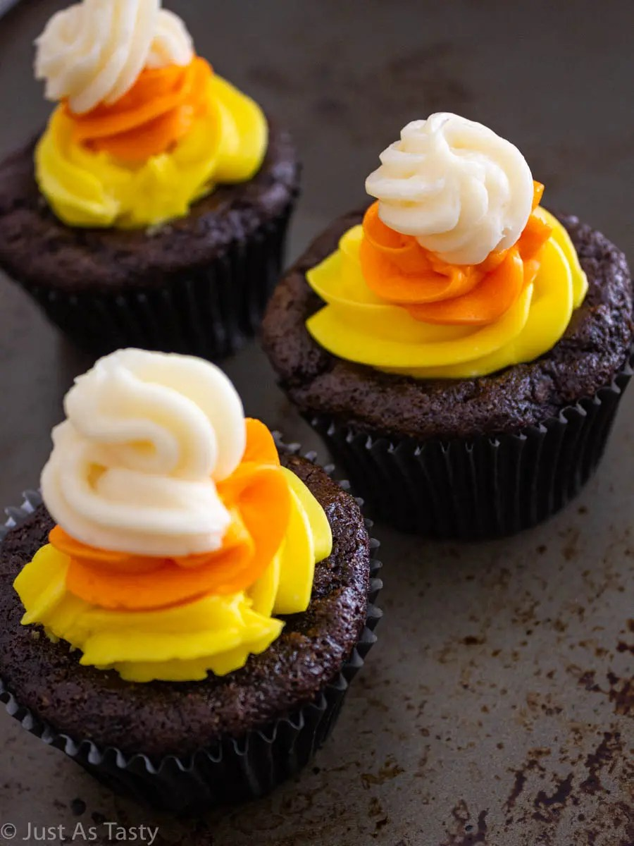 Three chocolate Halloween cupcakes topped with yellow, orange, and white swirl buttercream.