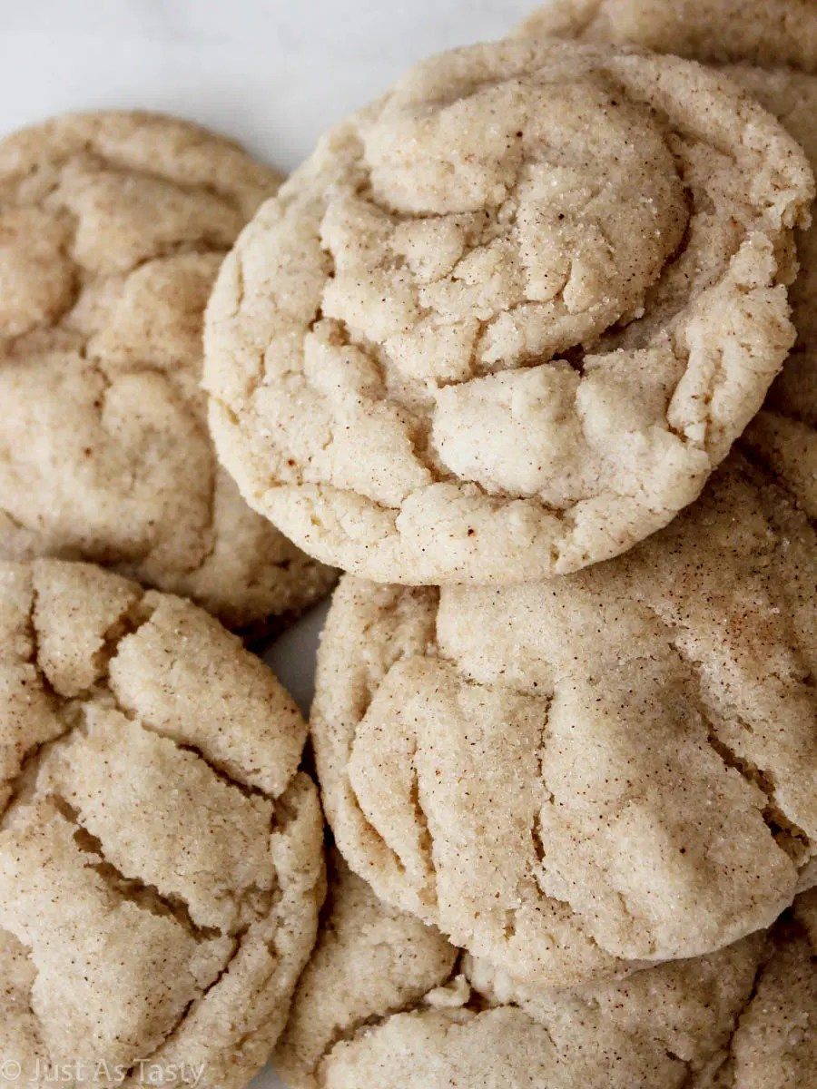 Close-up of gluten free snickerdoodles piled on a white plate.
