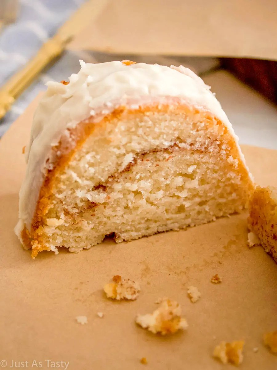 Slice of cinnamon roll cake on parchment paper.