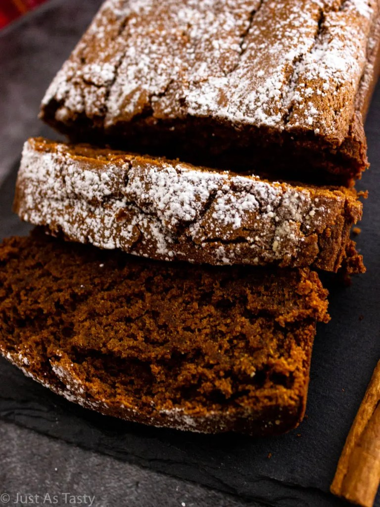 Close-up of sliced gluten free gingerbread loaf on a grey surface.