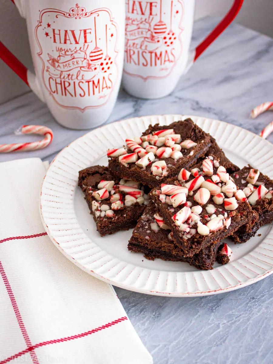 Peppermint brownies topped with candy canes on a white plate.