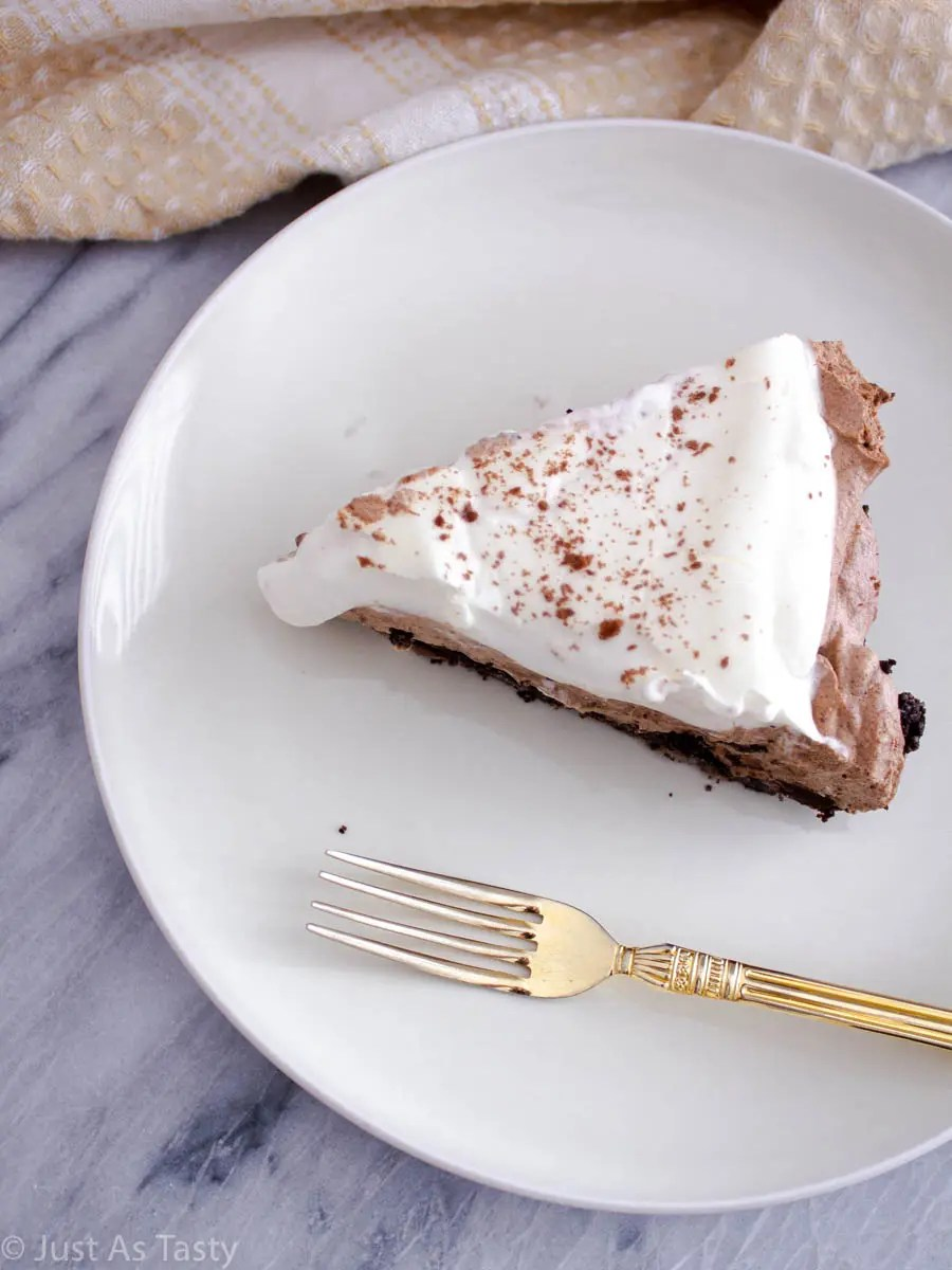 Slice of no bake chocolate mousse pie on a white plate with a gold fork.