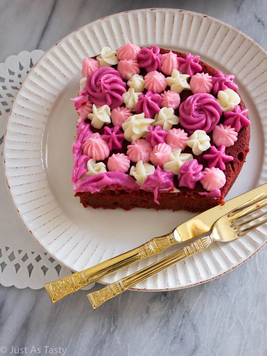 Slice of gluten free red velvet cake with pink and white piped frosting on top.