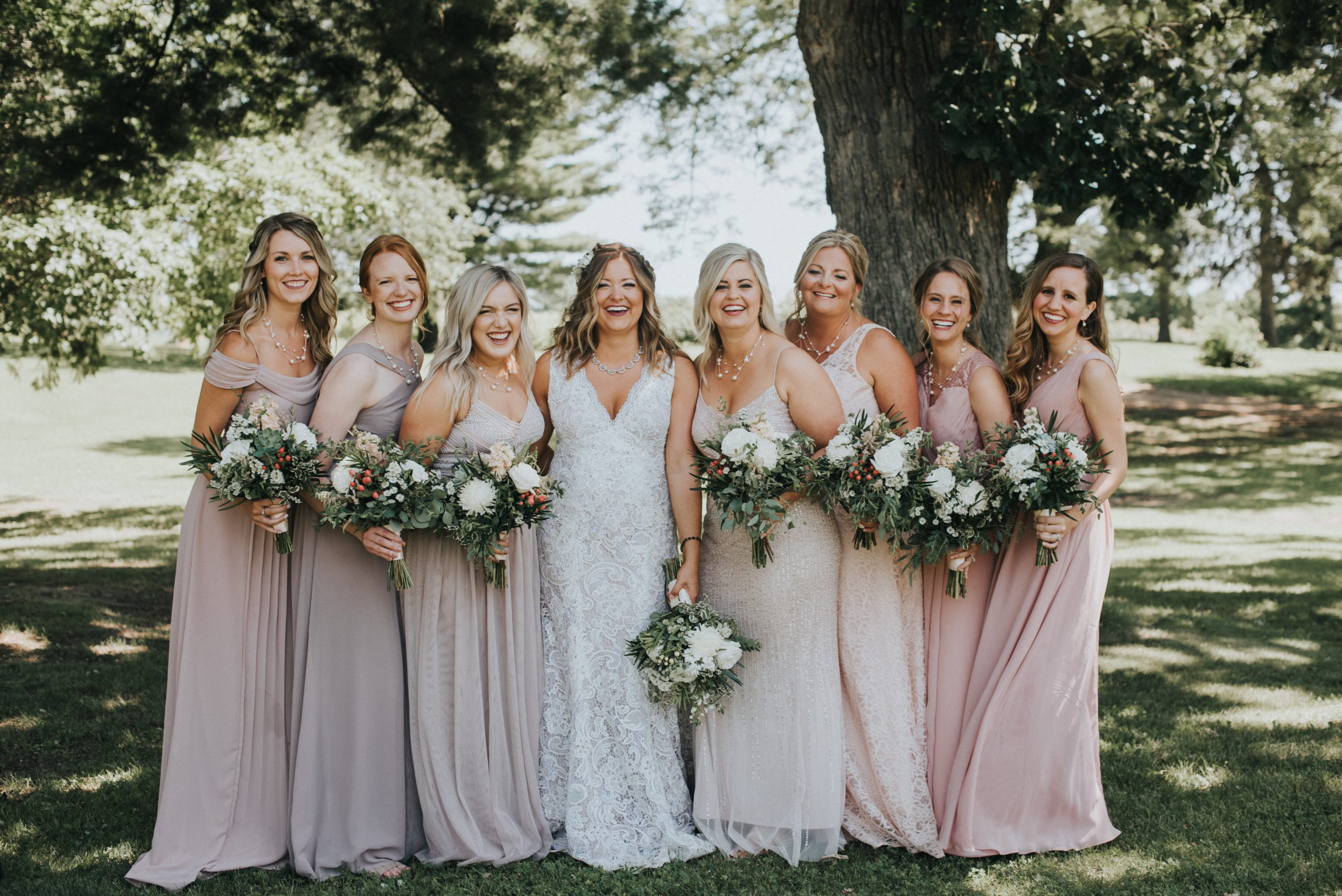 bride and her bridesmaids laugh at the camera