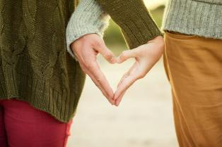young couple making a heart shape with their hands