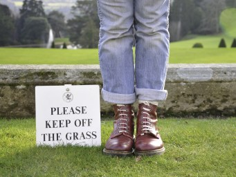 person standing on grass next to keep off the grass sign