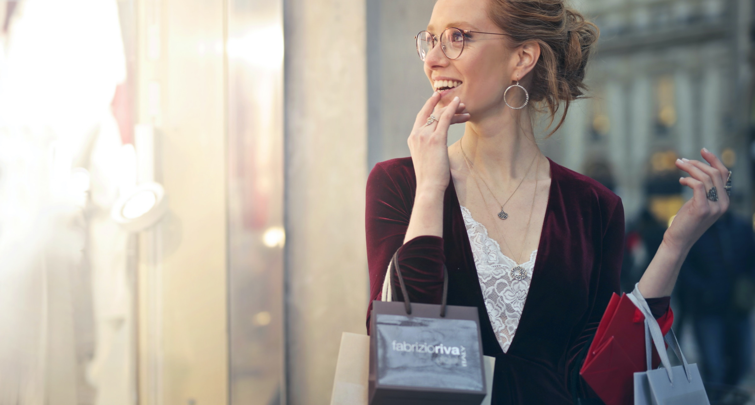 woman with shopping bags looking at another store's show widow