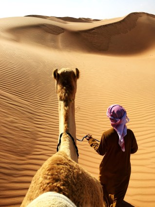 A man leaving a desert with a camel