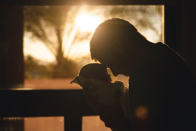 father praying over baby in the sunrise