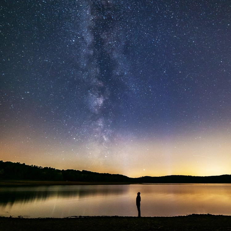 a man looking up at a starry sky