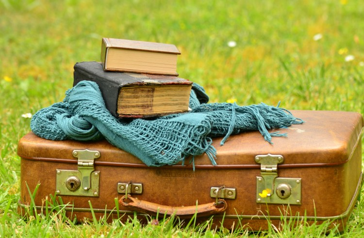 suitcase with a pile of books on top