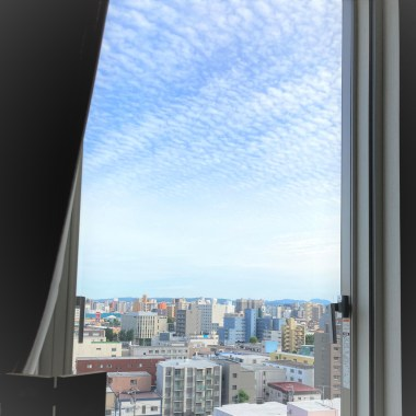 looking out over the city and blue sky from a hospital window