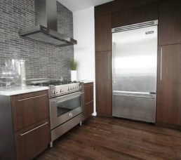 Deep brown wood cabinets with grey ceramic backsplash