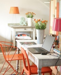 Rustic greying woods with pops of eclectic metal orange chairs