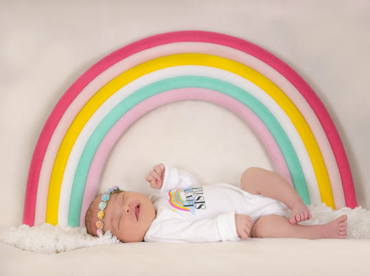 Rainbow Baby Violet Wears Her Little Sister Outfit while Laying Under a Rainbow. The baby after a child who passes away is known as the rainbow baby.