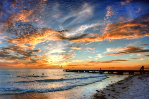 When I lived up north in the cold and then visited a warm place, I would savor the last remaining moments of my vacation. I think that's what was happening when I took this shot. A couple enjoying a last swim in the Gulf of Mexico one evening under a beautiful sunset in Bradenton Beach Florida. All good things come to and end, and fortunate for me I was here when it happened.