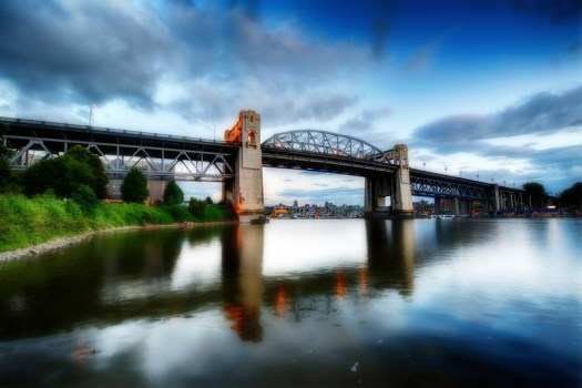 This is the Burrard Bridge in Vancouver. I shot this in the late afternoon when people were out walking and enjoying the scenery. This section of town is known as West End and it runs along False Creek into English Bay. If you look closely you'll see three ladies sitting on a log enjoying a picnic and the scenery of English Bay.