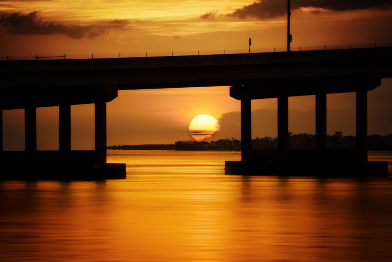 Near my house there are two bridges over the Mantee River, one older and one newer. The locals refer to the newer one as the green bridge, I suppose due to the paint on some of the girders. Nonetheless, from this spot on Bradenton's Riverwalk, the sun can be seen setting under the bridge as it sinks into the Gulf of Mexico. The end of another day.