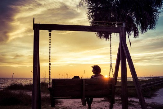 If you drive up and down the gulf coast of Florida it's amazing how many parks are named Sunset Park. But then you soon realize it's for good reason. This is a picture of my wife sitting on a swing with our dog Mr. Wiggles at Honeymoon Island State Park in Dunedin Florida. It was our first time here and we lucked out with a great sunset. We had meant to leave earlier, but when we noticed the clouds and the sun we just had to stay an extra hour to take it all in. Mr. Wiggles was fine with that.