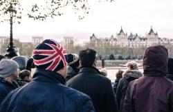 Man in Union Jack hat standing in crowd in London