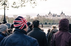 Man in Union Jack hat standing in crowd in London