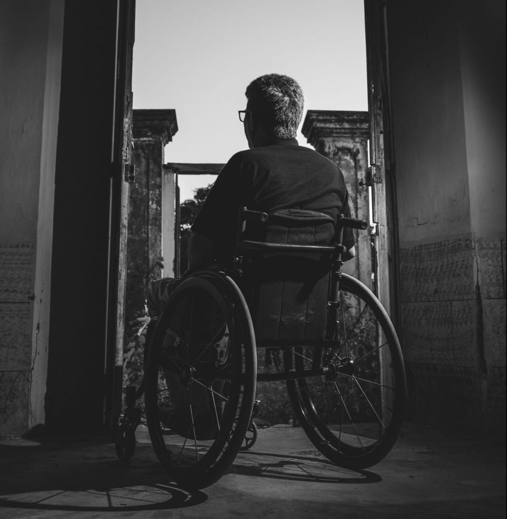 Man in wheelchair sitting in a doorway