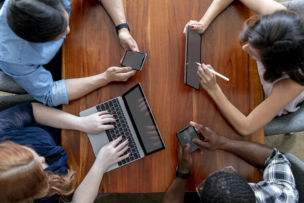 People sat at a table using technical devices