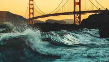 low angle shot of strong waves crashing on the shores under golden gate bridge