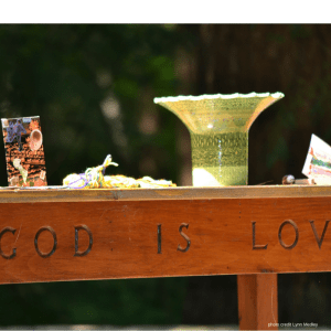 "this photo is of a brown wood table, on which is engraved ""God is love"". in top are objects - shells, a chalice, and feathers. It was taken by L. Medley and used with permission"
