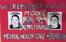 "Red protest poster reads ""We Remember Kayla Moore, Demilitarize Mental Health Care in Berkeley"" Kayla is pictured in two photos. She flashes a peace sign and grins in one. On the other, she's smiling, maybe playfully, and holding a telephone. She's wearing a Mickey Mouse shirt. Two black and white silhouette drawings of Kayla are on either side of the photos. The drawings are made by Oree Originol and read ""Justice for Kayla Moore"""