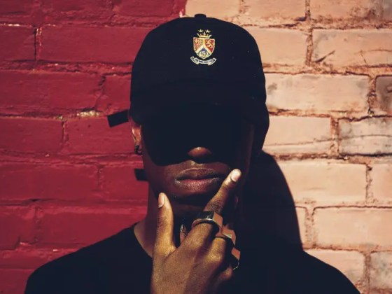 """""""A man wearing a baseball cap, brass knuckles and earrings holding his chin by a brick wall"""" by Andre Hunter on Unsplash"""
