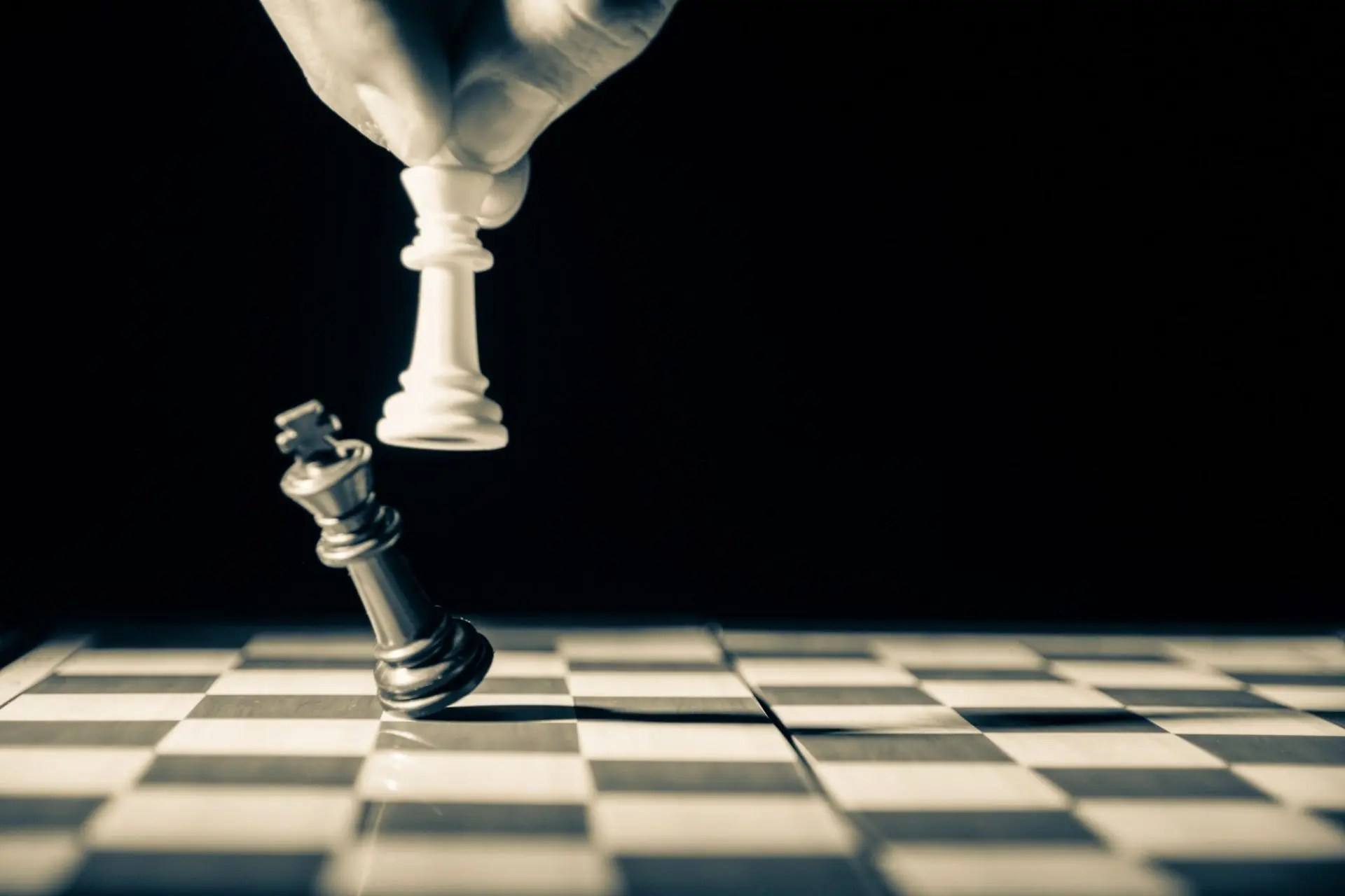 One chess piece knocking over another on an empty chess board