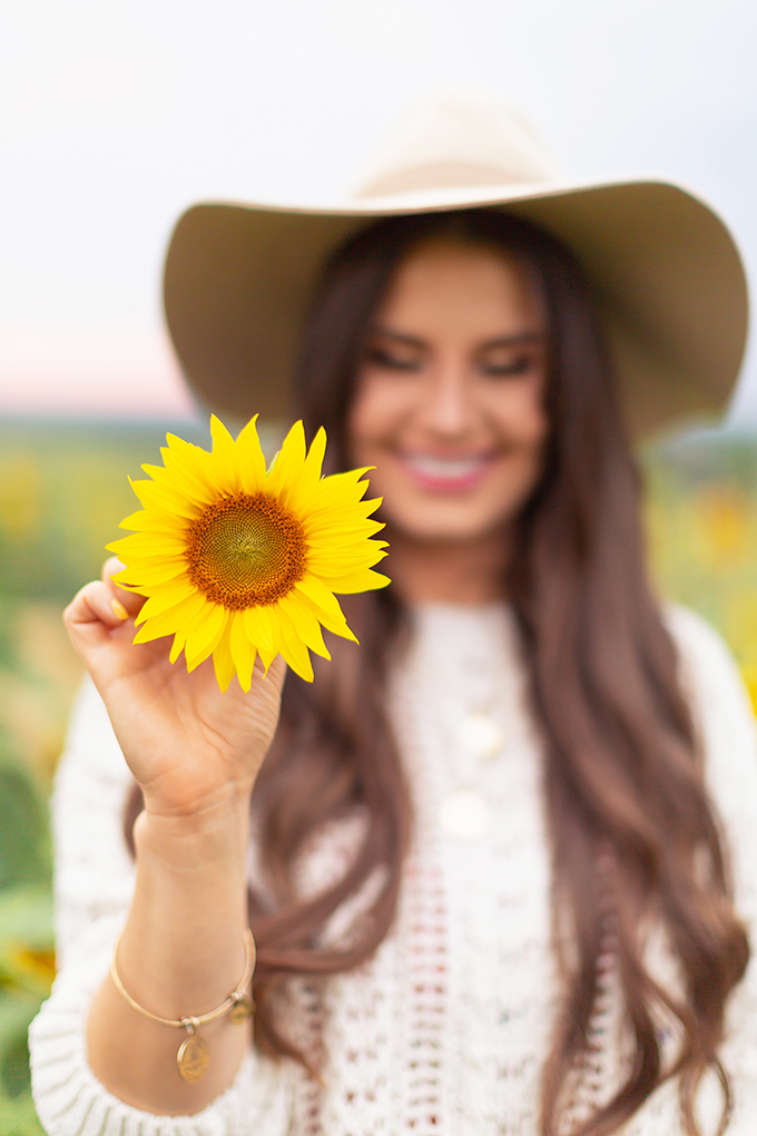 September 2018 Soundtrack | Girl wearing a Hat Holding a Sunflower and Smiling in the Bowden Sunmaze at Sunset, Alberta, Canada | Calgary Lifestyle Blogger // JustineCelina.com