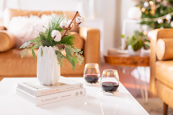 Apartment Friendly Modern Holiday Decor   Simple Holiday Arrangement on a Coffee Table with Greenery and Cotton Stems and 2 glasses of red wine with a Christmas Tree in the Background   Bohemian, Mid Century Modern Holiday Decor   Bohemian Holiday Home Tour 2018   Canadian Tire CANVAS Ornaments // JustineCelina.com