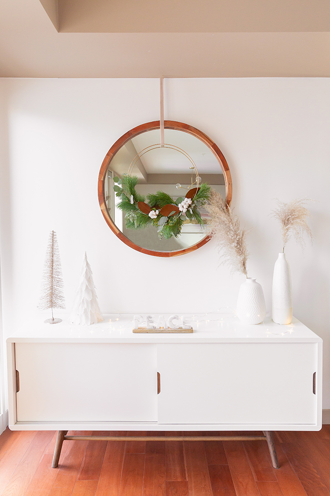 Apartment Friendly Modern Holiday Decor | DIY Modern Holiday Wreath with Magnolia Leaves, Cotton, Silver Dollar Eucalyptus, Seeded Eucalyptus, Cedar and Insense Cedar | Bohemian Holiday Home Tour 2018 | Caramel Mid Century Modern Leather Couches | Canadian Tire CANVAS Ornaments // JustineCelina.com