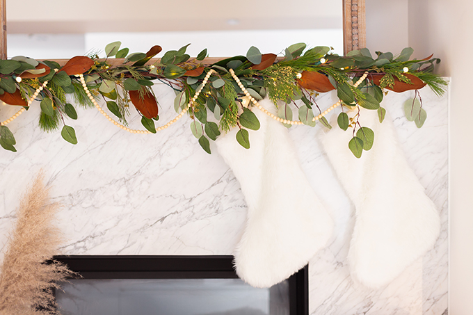 Apartment Friendly Modern Holiday Decor | Canadian Tire CANVAS Pre-lit Eucalyptus Leaves Garland with added greenery, magnolia leaves and wooden beads | Marble Fireplace | Bohemian, Mid Century Modern Holiday Decor | Simple Holiday Arrangement on a Coffee Table with Greenery and Cotton Stems | Bohemian, Mid Century Modern Holiday Decor | Bohemian Holiday Home Tour 2018 | Caramel Mid Century Modern Leather Couches | Canadian Tire CANVAS Ornaments // JustineCelina.com